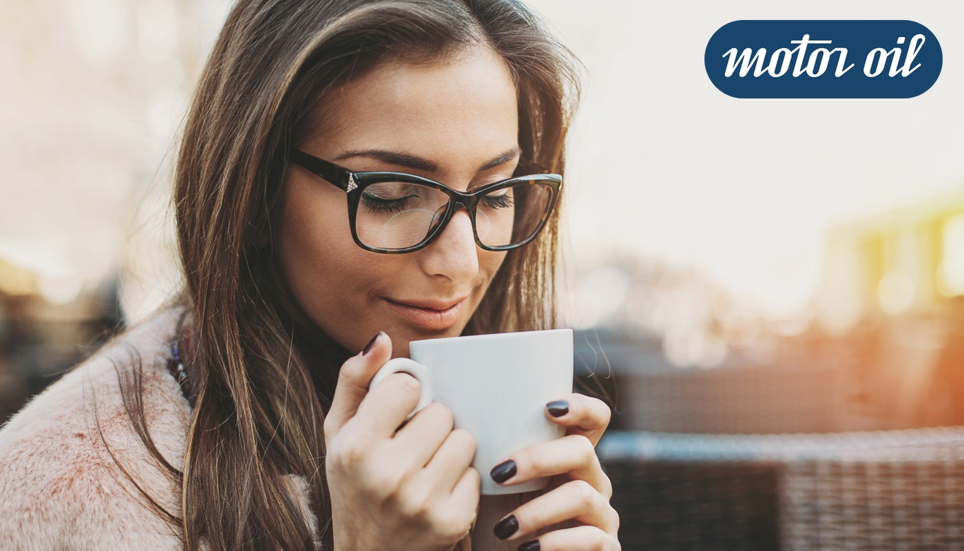 Mujer con lentes Motoro Oil jeans tomando cafe
